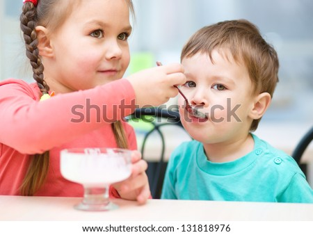 Girl is feeding his little brother with ice-cream in parlor - stock photo
