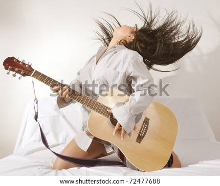 girl is feeling free and playing guitar in a room