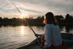 Girl is fishing with a fishing rod. Girl is sitting in the boat. Fishing at the shore of the lake.