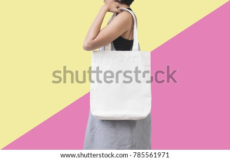 Girl is holding bag canvas fabric for mockup blank template isolated on color background.