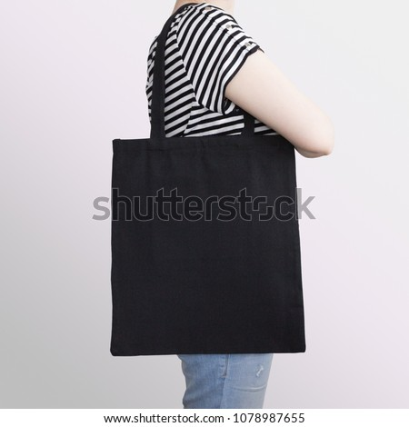 Girl is holding black cotton eco tote bag, design mockup.
