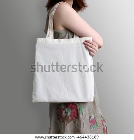 Girl is holding blank cotton eco tote bag, design mockup. Handmade shopping bag for girls.
