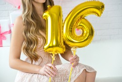 Girl is holding the balls of the number 16. The birthday of sixteen years.