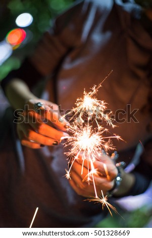 Girl is holding two sparking firecracker together #501328669