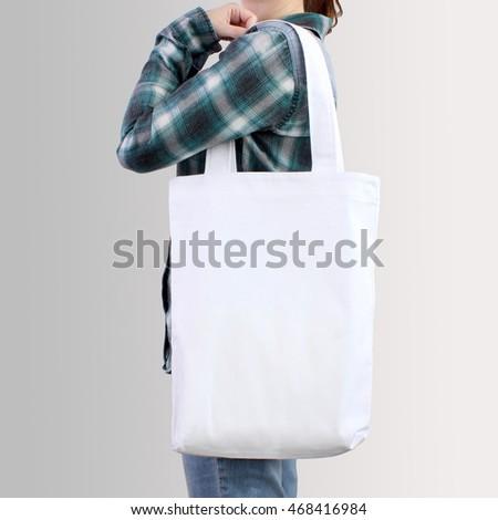 Girl is holding white blank cotton tote bag, design mockup. Handmade shopping bag for girls.