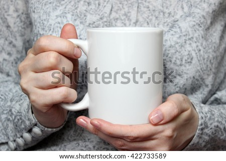 Girl is holding white cup in hands. Mug for woman, gift. Mockup for designs. #422733589