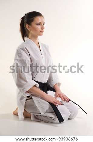 girl is in a kimono.punch.figure in the karate fighting stance on a white background.