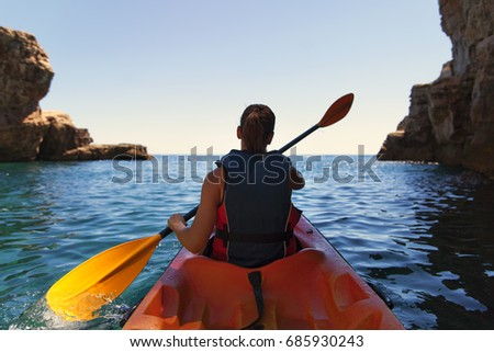 Girl is kayaking on the adriatic sea