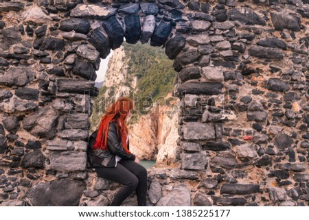 Girl is looking outside the old window. The window is located over a cliff near Portovenere near the famous Cinque Terre  #1385225177