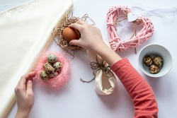 girl is make wickerwork of beads and eggs for easter