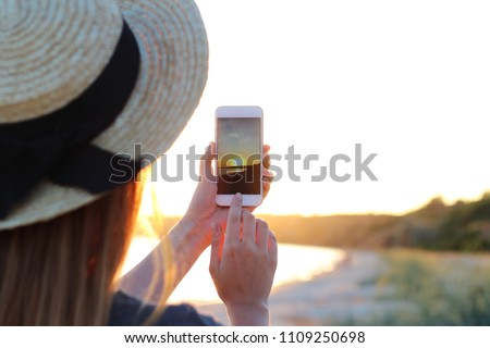 girl is making a photo of a sunset on a modern smartphone on the background of the sea