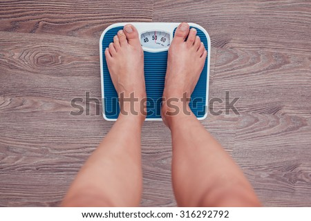 Girl is measuring her weight on the scales.