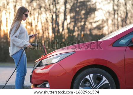 Girl is plugging electric vehicle for charging car battery at parking. Plugged charging cable electric vehicle. EV parking, power charger cable, charging port station.