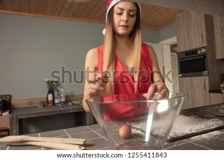 girl is preparing cake for Christmas, putting eggs , front view