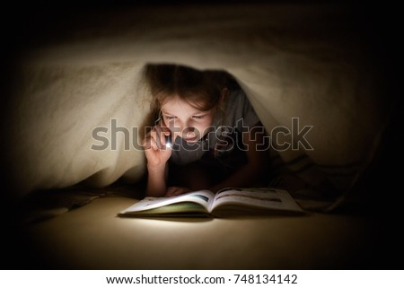 girl is reading a book under a...