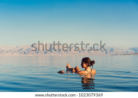 Girl is relaxing and swimming in the water of the Dead Sea in Israel #1023079369