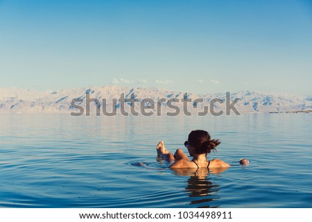 Girl is relaxing and swimming in the water of the Dead Sea in Israel #1034498911