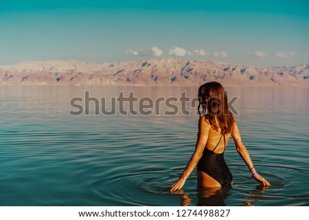 Girl is relaxing and swimming in the water of the Dead Sea in Israel #1274498827
