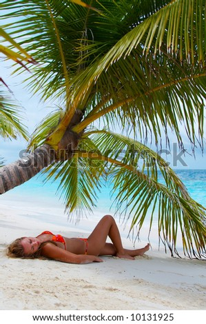 Girl is relaxing on the beach. Island of Paradise. White sand beaches with palm trees and crystal blue water. Maldives. Luxury holidays.
