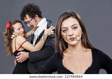 girl is sadly looking while her boyfriend flirts with another woman