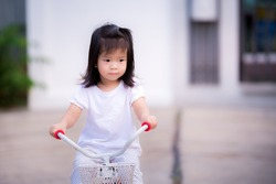 Girl is sadly riding bicycle from social distancing in epidemic pneumonia situation. She doesn't have friends of the same age to run around and talk to. Asian children lonely and depressed.