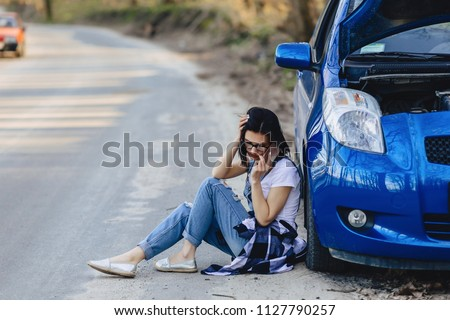 girl is sitting by car with an open hood and speaks by phone on road alone