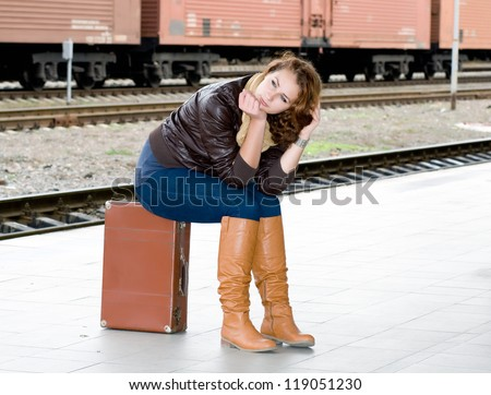 girl is sitting on a suitcase waiting for the train