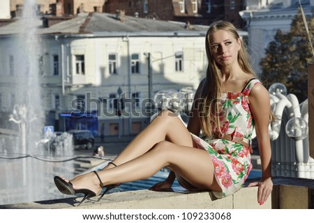 girl is sitting on parapet on background of old town with a two-story houses.