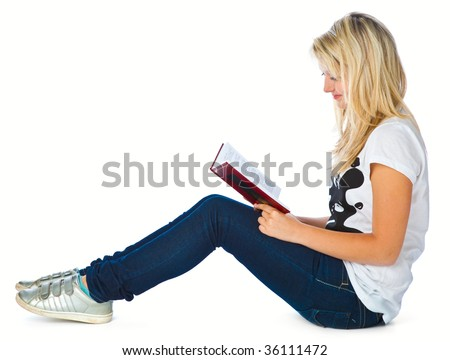 Girl is sitting on the floor and is reading book. Isolated on white background