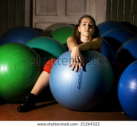 girl is sitting with a ball on the floor in the gym