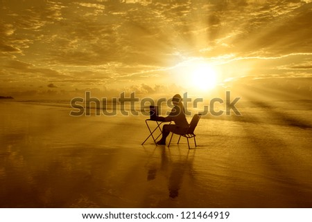 Girl is sitting with her laptop under beautiful sunset on the beach