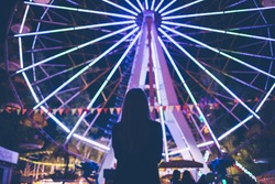 Girl is staying near Ferris wheel in the evening park and looking on colorful eye