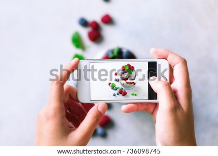 Girl is taking photos of breakfast, chia pudding with berries to mobile phone. Social media, instagram concept. Copy space, top view