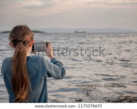Girl is taking picture of cruise ship in a bay, Girl is in focus, Cruise liner is out of focus. Muted colors,
