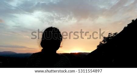 girl is watching the sundown #1311554897