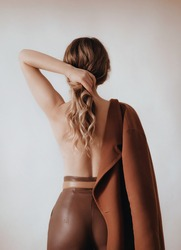 Girl  is with a bare back in a trendy spring set of beige and brown clothes. Natural colors. Trend of 2021 total  beige.