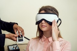 Girl is worried for her sight. Relaxed modern european woman sitting in office of eye care specialist waiting when procedure will be finished, wearing digital vision screener during check-up