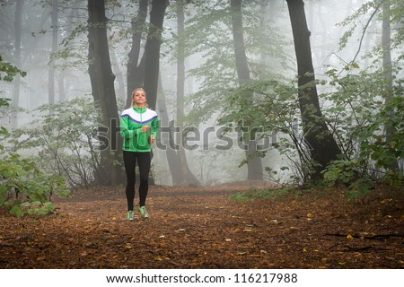 girl jogging in autumnal woodland with fog