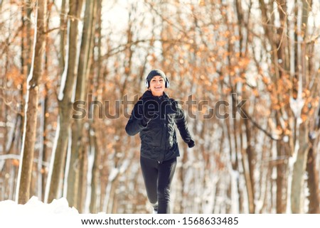 Girl jogging in the snow on the nature in winter