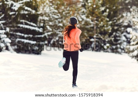 Girl jogging in the snow on the nature in winter.Back view