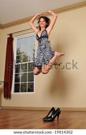Girl jumping and having fun indoors with high heels on the floor