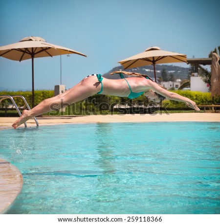 Girl jumping from a board of a swimming pool to the water. Summer fun and sport concept #259118366
