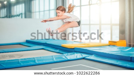 Girl jumping high in striped tights on big trampoline. Stock fotó ©