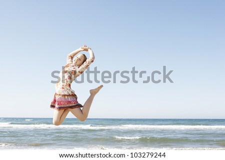 Girl jumping in the air on a beach with a blue sky in the background.