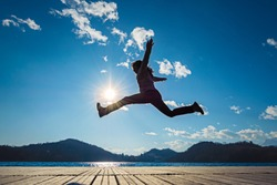 Girl jumping in the sun on the dock of a lake
