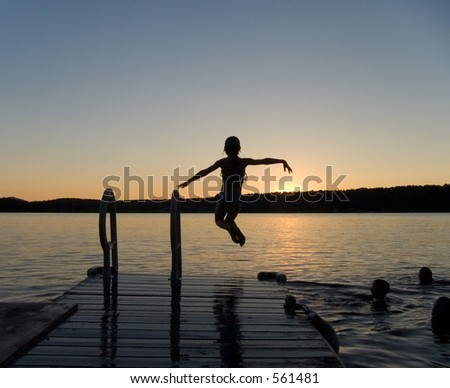 Girl jumping off a pier at dusk