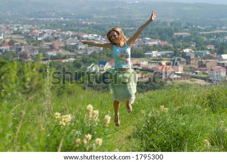 Girl jumping on a green hill against the industrial background