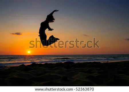 girl jumping on beach in sunset