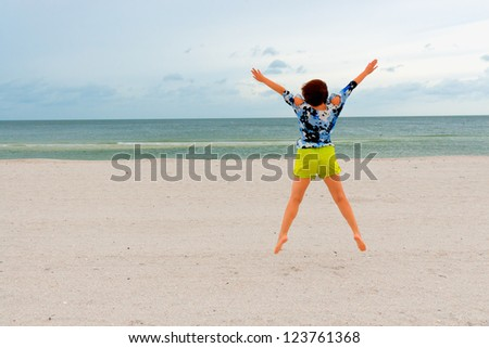 Girl jumping on the beach on windy day. Gone with the wind.