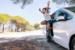 Girl jumps out of the car door with a face mask and sunglasses happy with her arms open for having been able to enjoy the summer vacations after the coronavirus covid19 pandemic on a road